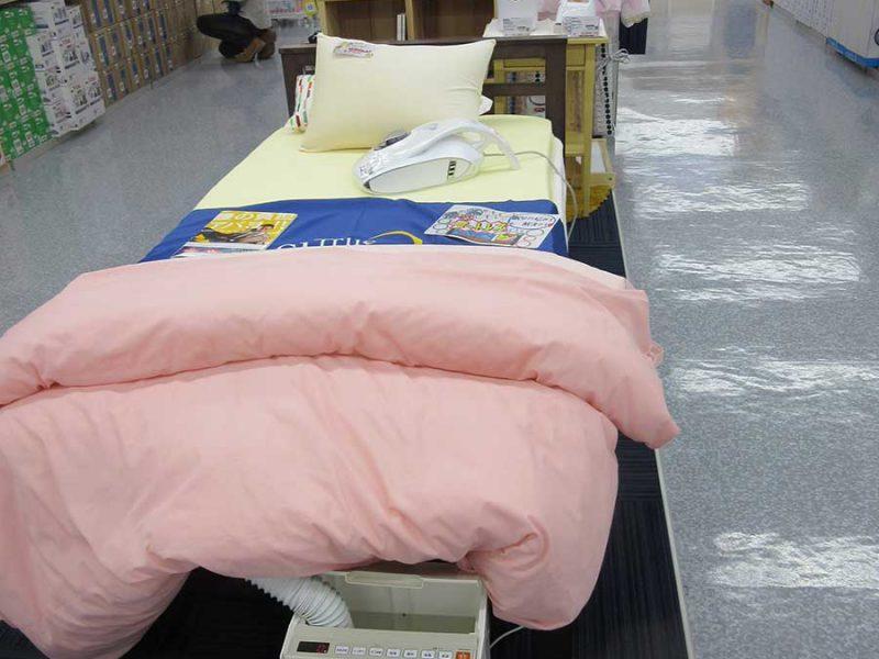 ベッドを置き、手前にふとん乾燥機、敷き布団の上のふとんクリーナー、奥のサイドスタンドには加湿器類を配置して快適な眠りを提案